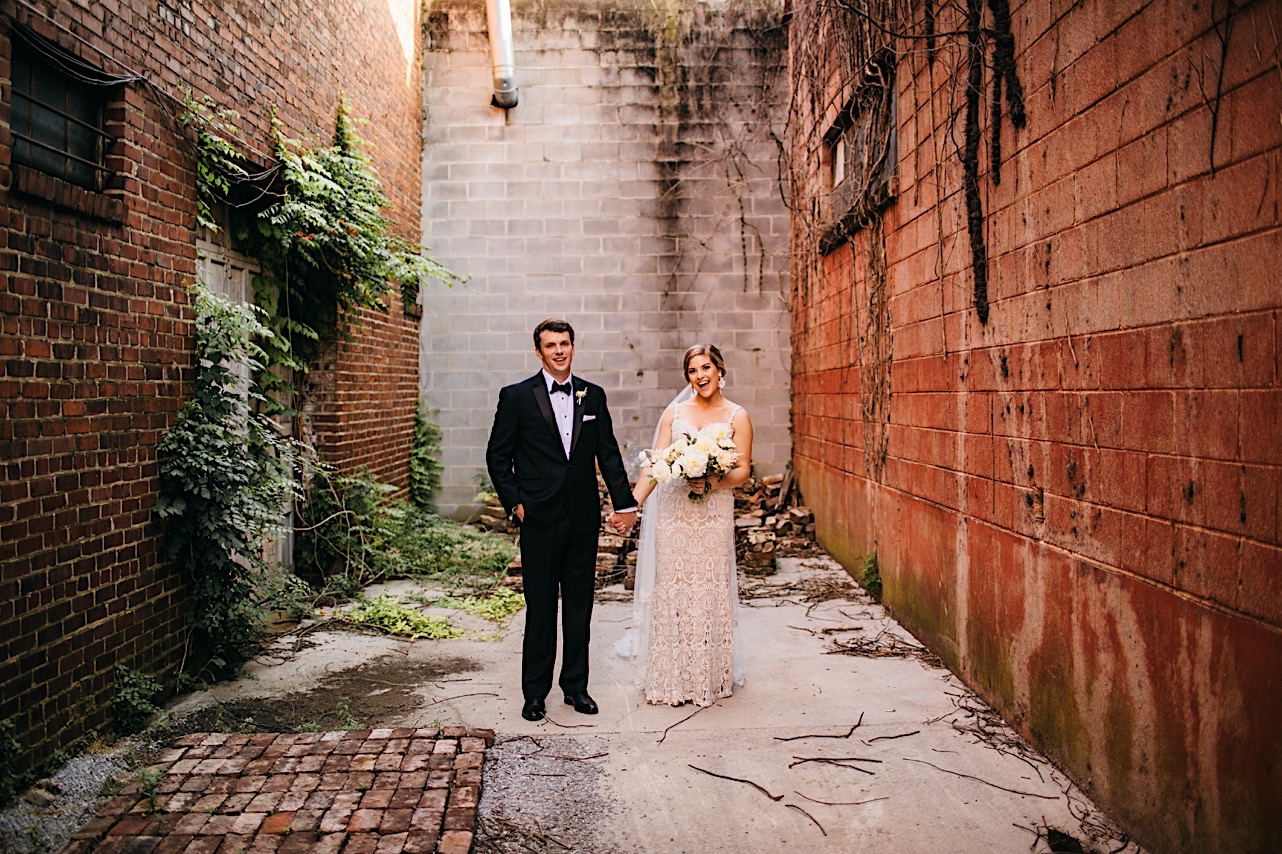 bride and groom hold hands in a narrow brick alleyway behind downtown Chattanooga's Turnbull Building