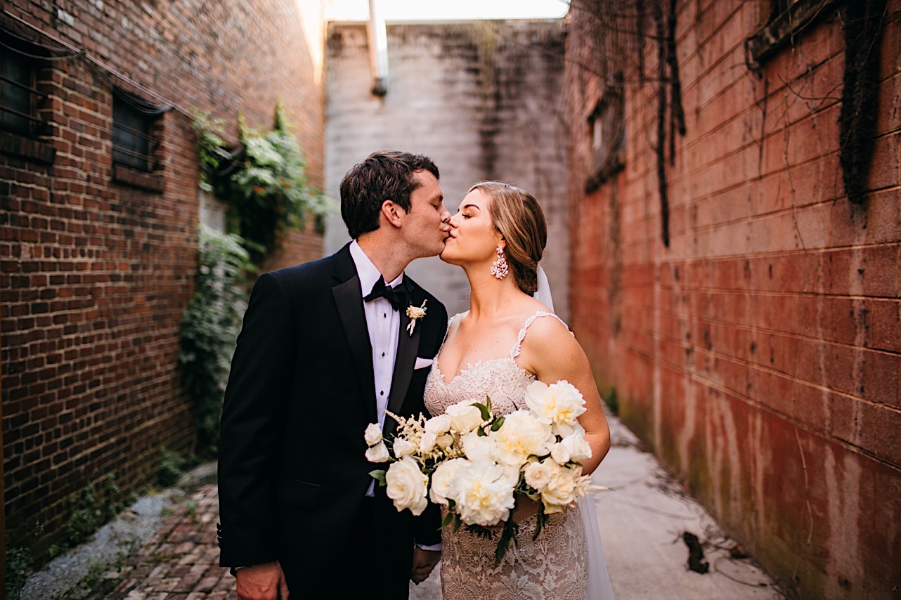 bride holds large Petaline bouquet of white flowers and kisses groom in narrow brick alleyway behind The Turnbull Building