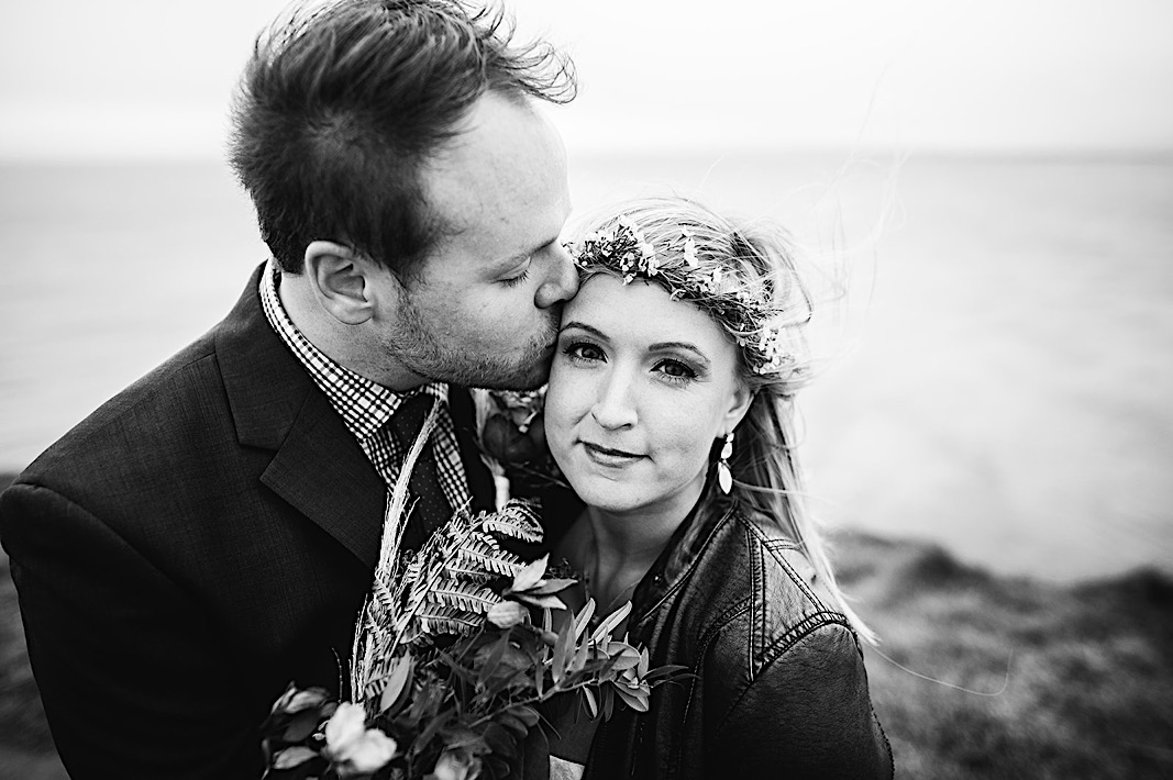Groom kisses the bride's temple as she smiles during their elopement photos at the Moher Cliffs