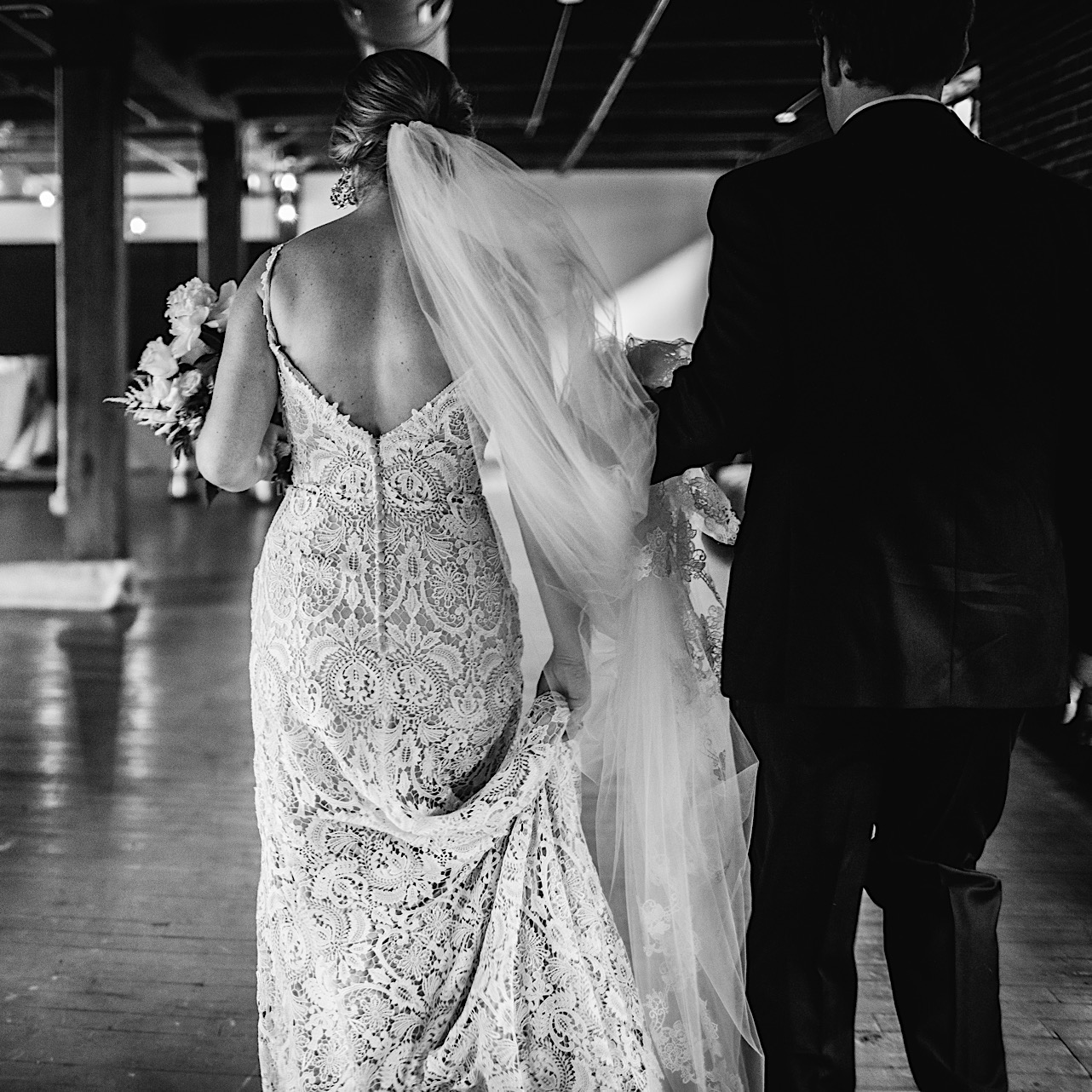 bride carries the train of her low-back lace wedding gown next to groom carrying her long, sheer veil in his hand
