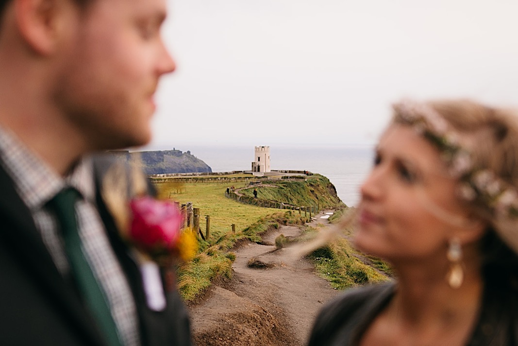 Bride and groom gaze into each other's eyes as they stand on the cliffside of the Moher Cliffs