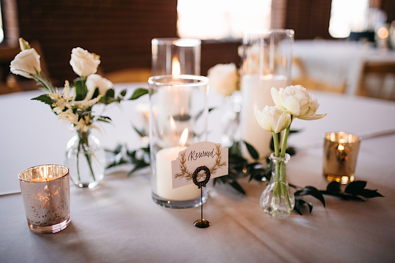 Tabletop Reserved sign next to candles and short glass vases with white flowers
