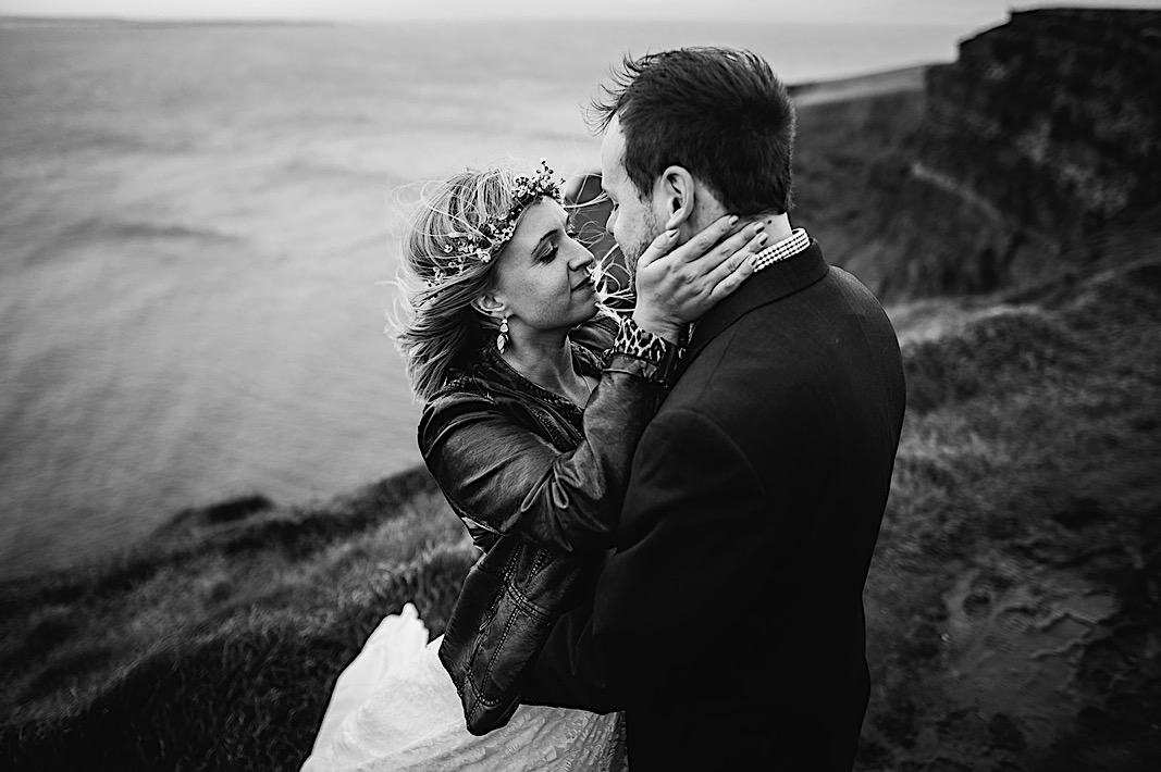 Bride holds grooms face and gazes lovingly at groom during their elopement photos at the Moher Cliffs