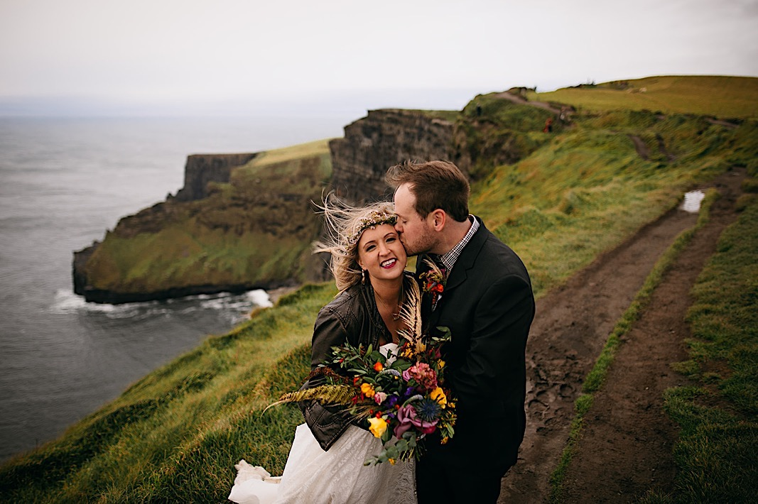 Groom kisses the brides temple as she smiles during their elopement photos at the Moher Cliffs