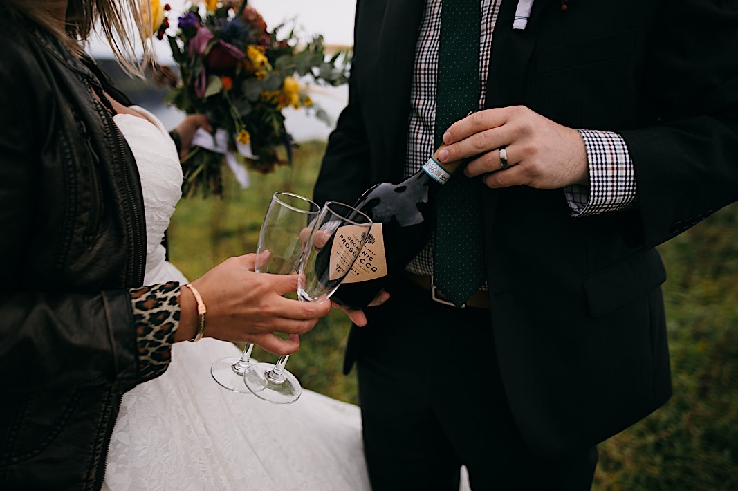 Bride holds two champagne glasses as groom grabs a bottle of Prosecco during their elopement photos at the Moher Cliffs