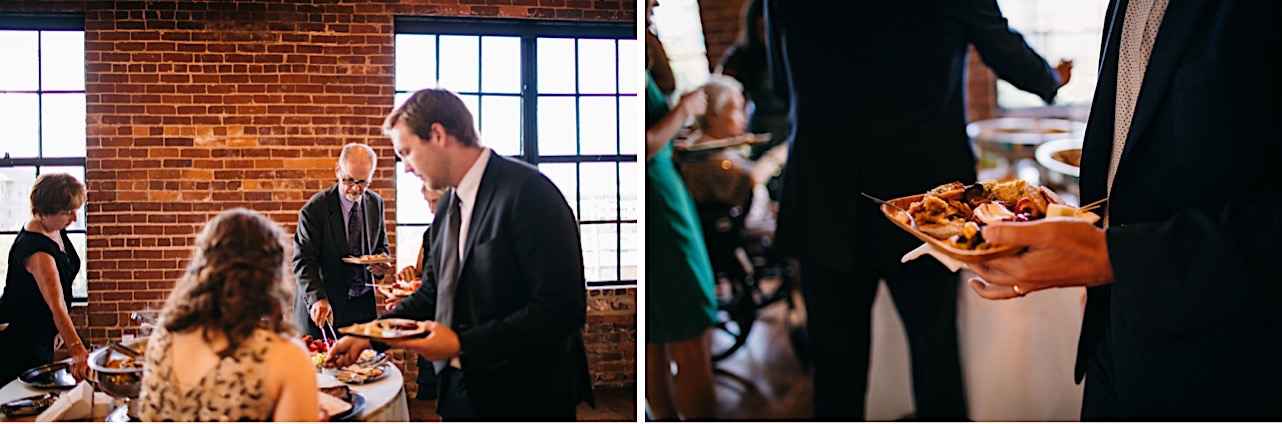 wedding guests select food from buffet tables next to exposed brick walls and tall windows