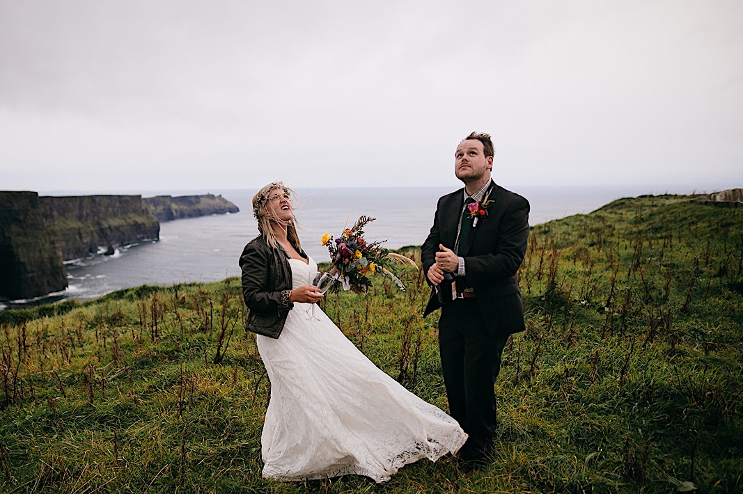 Groom pops a bottle of champagne of the cliffside of the Moher Cliffs