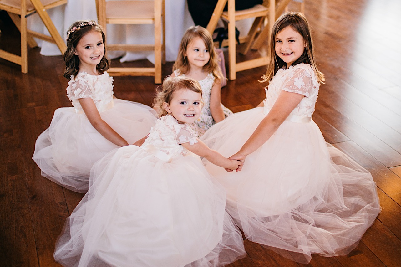Four small girls in white tulle dresses sit on a wooden floor holding hands with each other