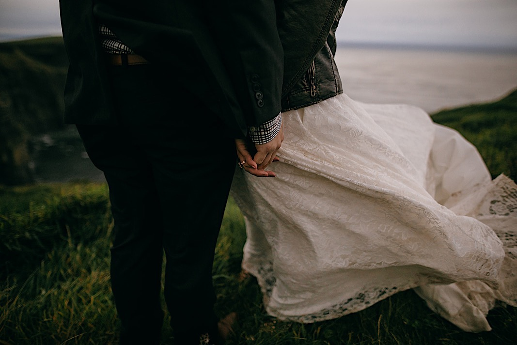Close up of the bride and groom holding hands as her white lace wedding dress sways in the wind at the Moher Cliffs