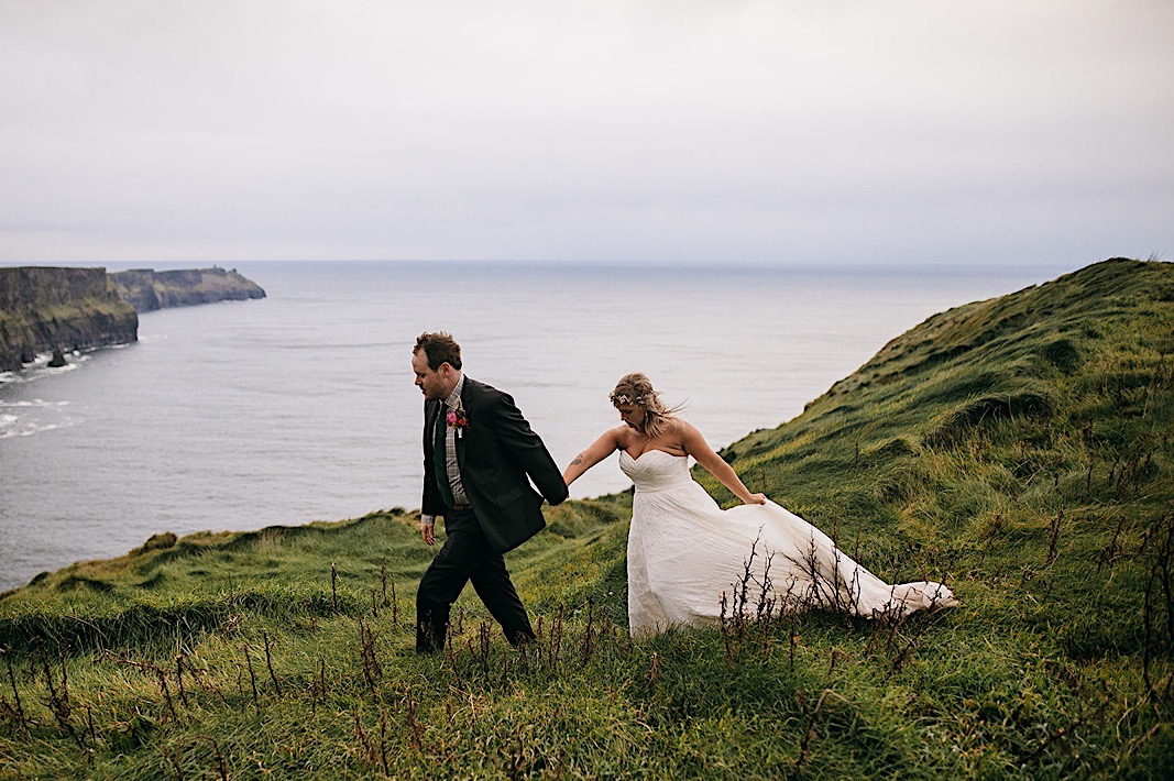 Bride and groom hold hands as they walk down the cliffside of the Moher Cliffs