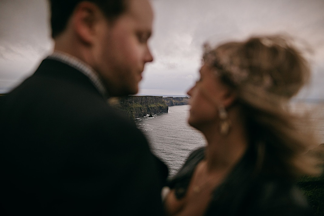 Bride and groom gaze lovingly at each other during their elopement photos at the Moher Cliffs
