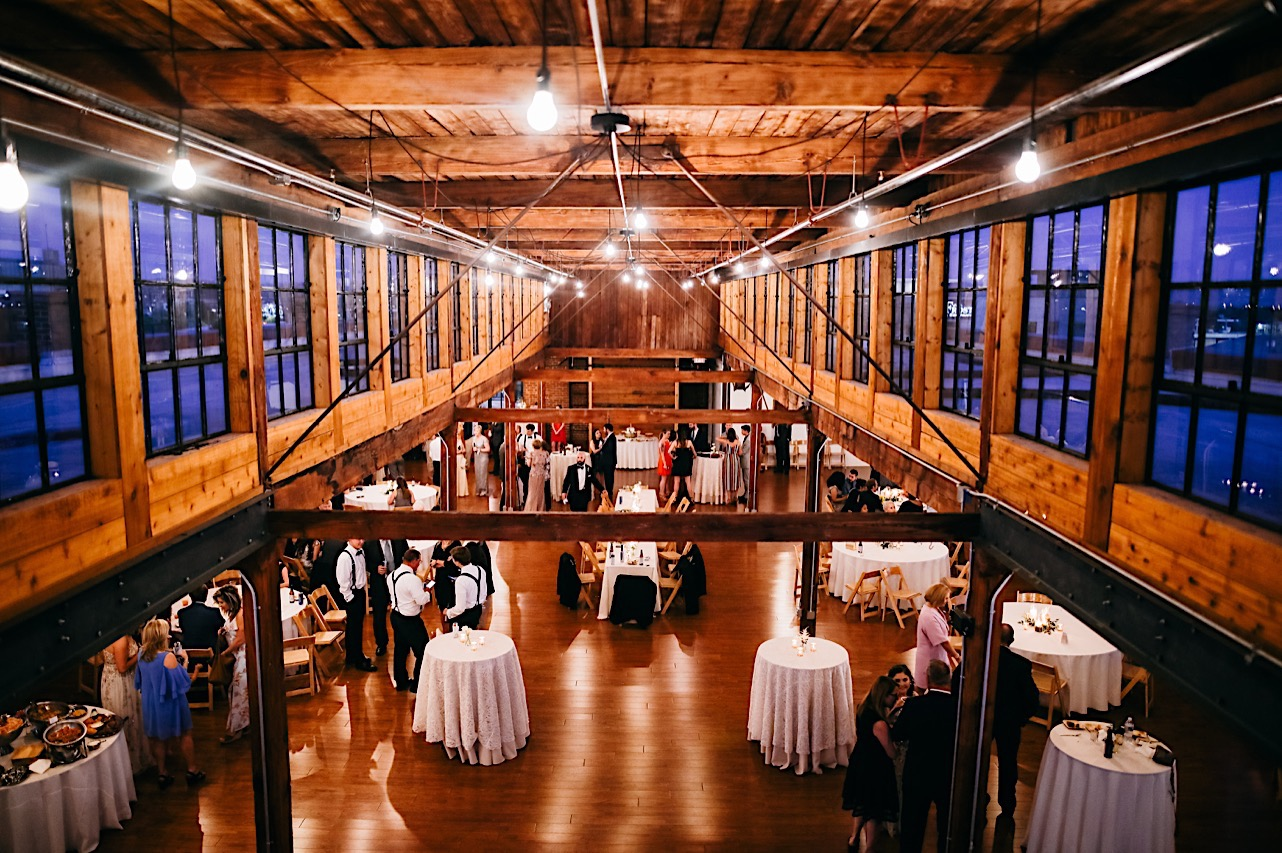 The Turnbull Building set for a wedding reception with white-clothed tables under exposed beams and high windows