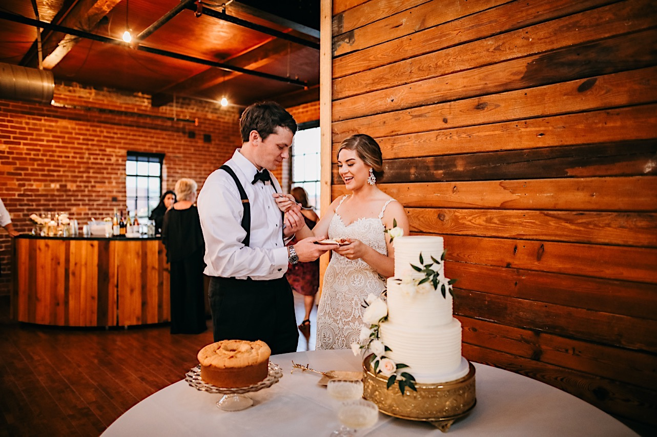 standing in front of shiplap wall at The Turnbull, bride and groom hold a plate of cake next to 3-tier white wedding cake