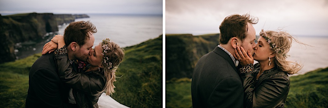Groom looks back towards the bride as they hold hands and walk down the cliffside of the Moher Cliffs