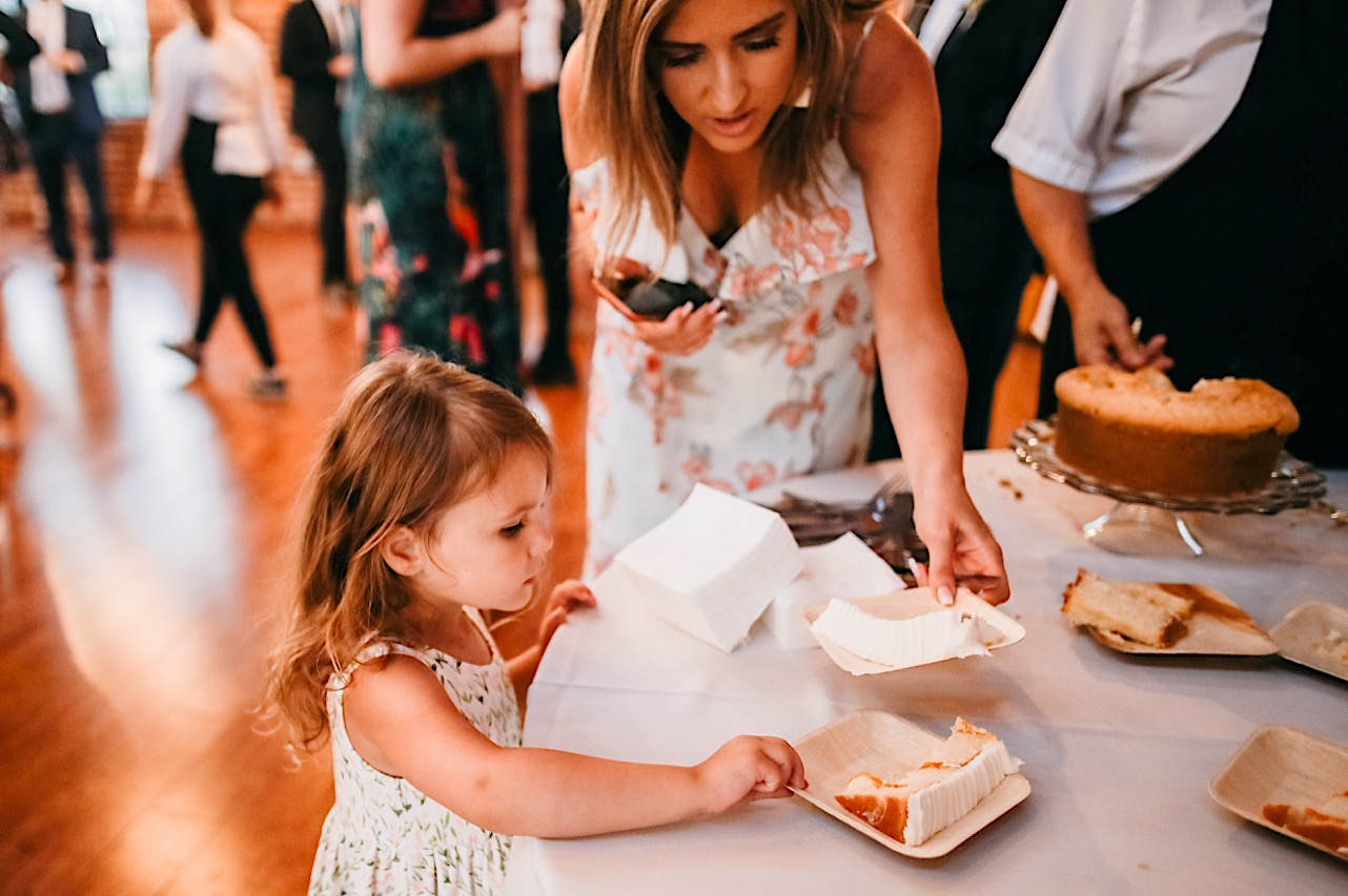 woman helps a small girl choose a piece of cake from a table