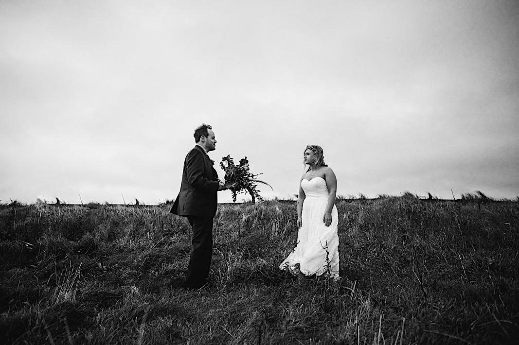 Groom holds brides bouquet as she walks towards him at the Moher Cliffs