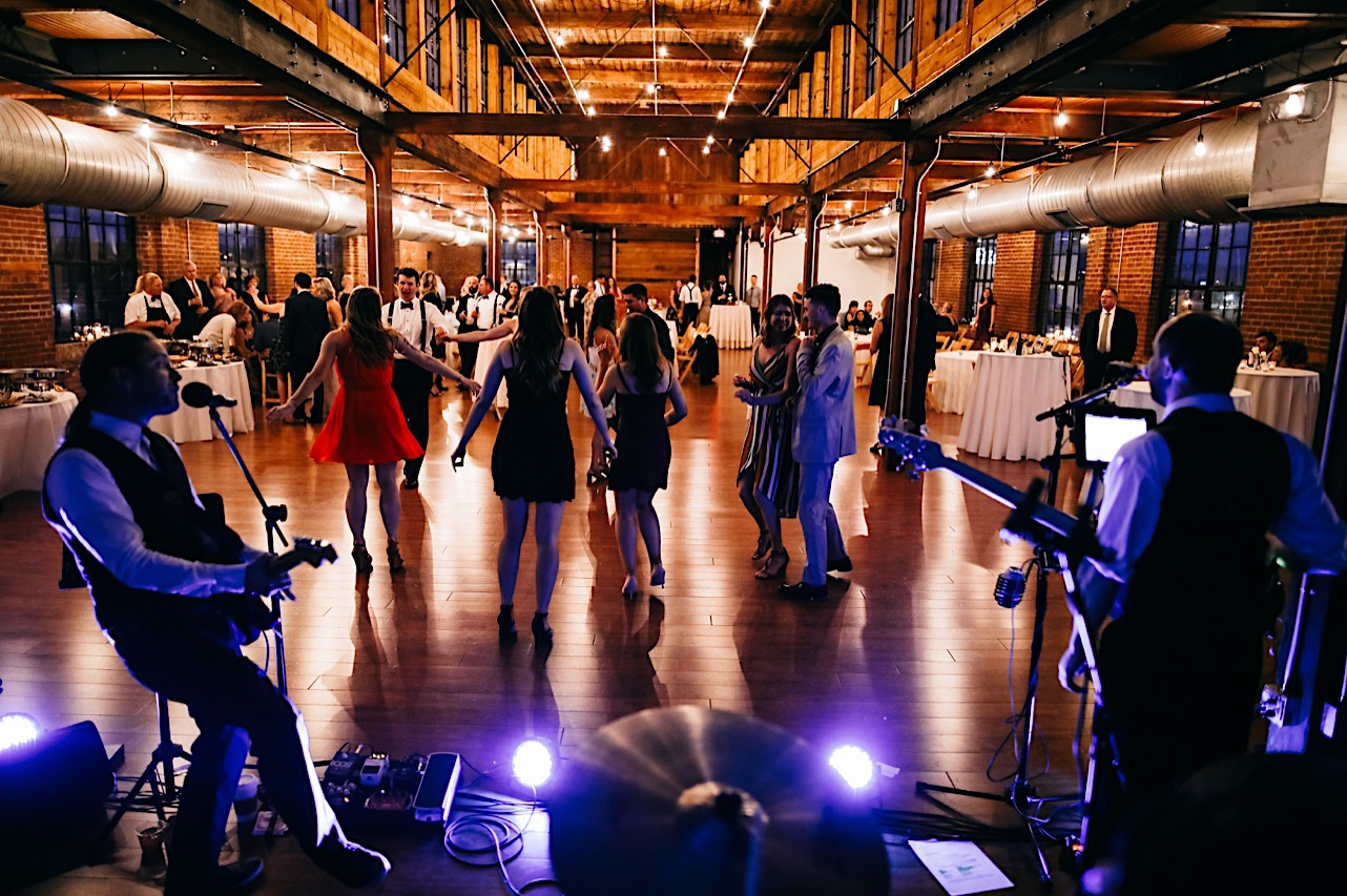 wedding guests dance in the evening light at The Turnbull Building while live band plays