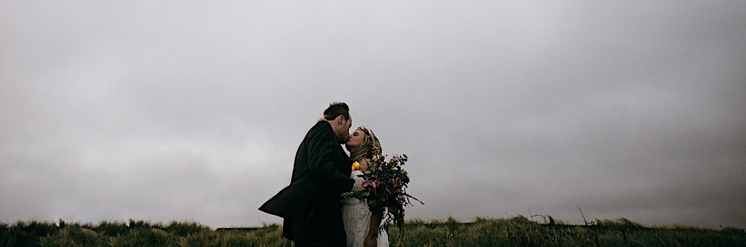 Groom gives bride a kiss at the Moher Cliffs