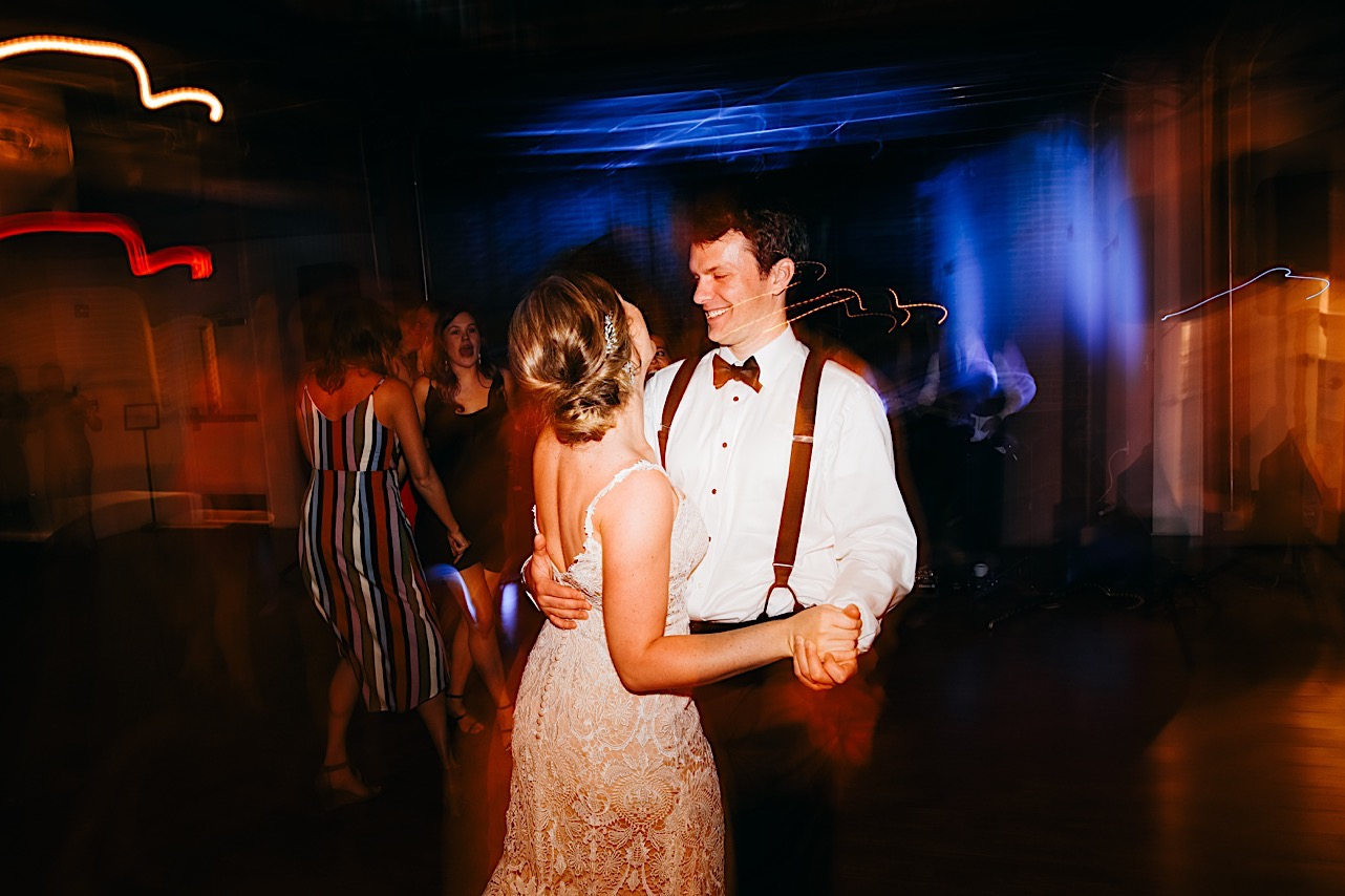 bride in low-back lacy wedding dress dances with groom in white shirt, black bowtie, and black suspenders