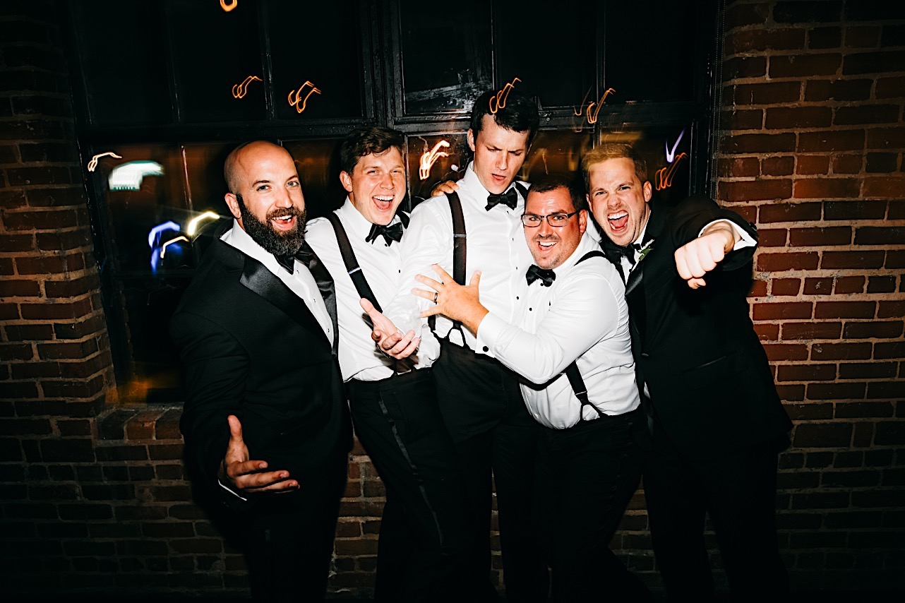groom and groomsmen sing and dance near a tall window