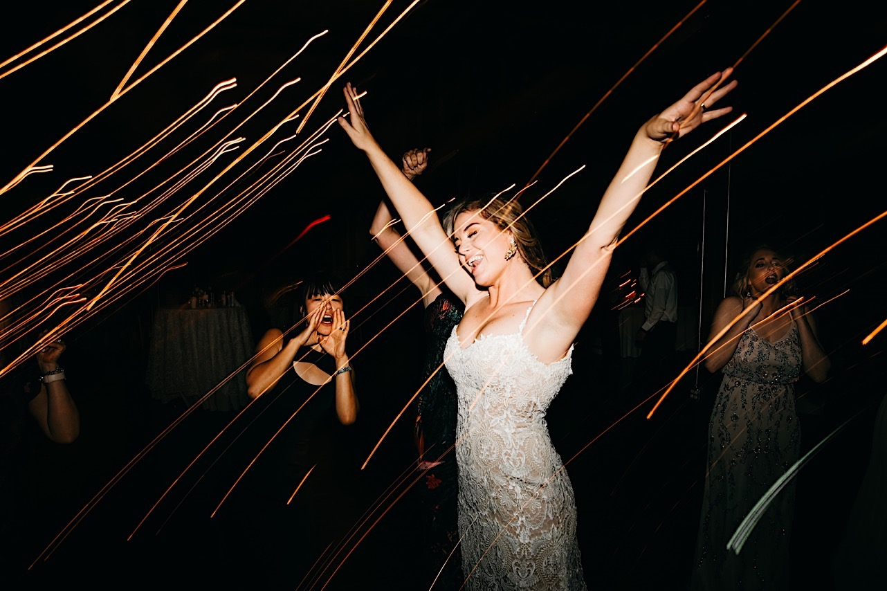 bride in lacy wedding gown dances with her hands in the air while friends cheer nearby