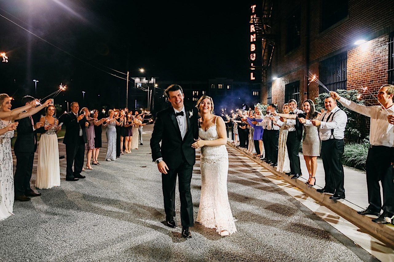 after their wedding bride and groom walk between friends with sparklers outside The Turnbull Building in downtown Chattanooga