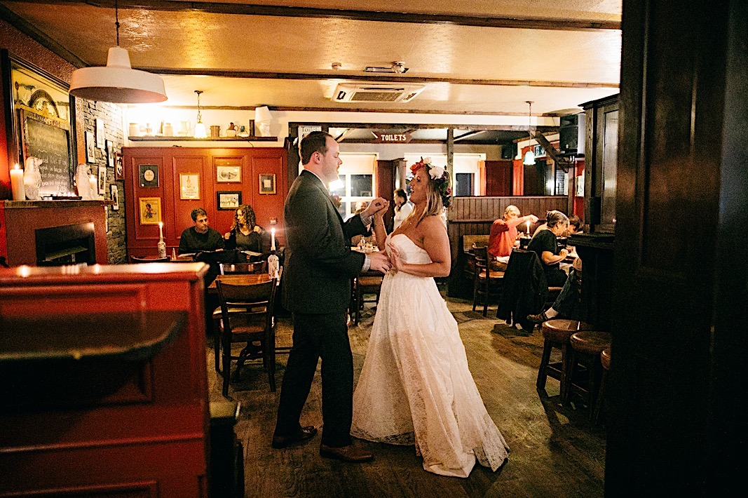 Bride and groom laugh during their first dance in an Irish restaurant