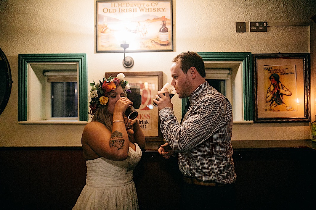 Bride and groom drink together during after their elopement on the Cliffs of Moher