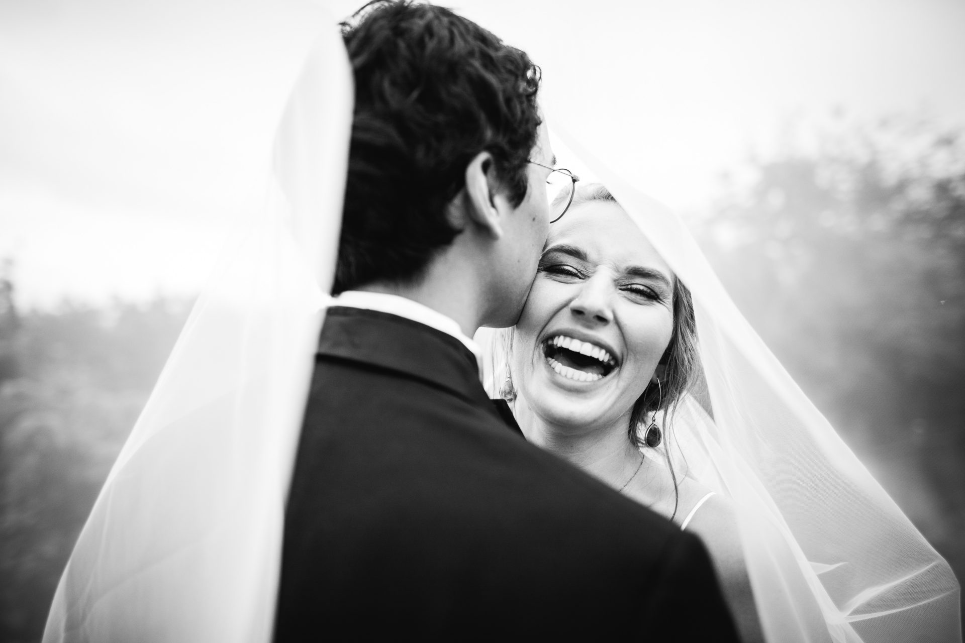 groom kisses brides temple underneath her veil while she laughs