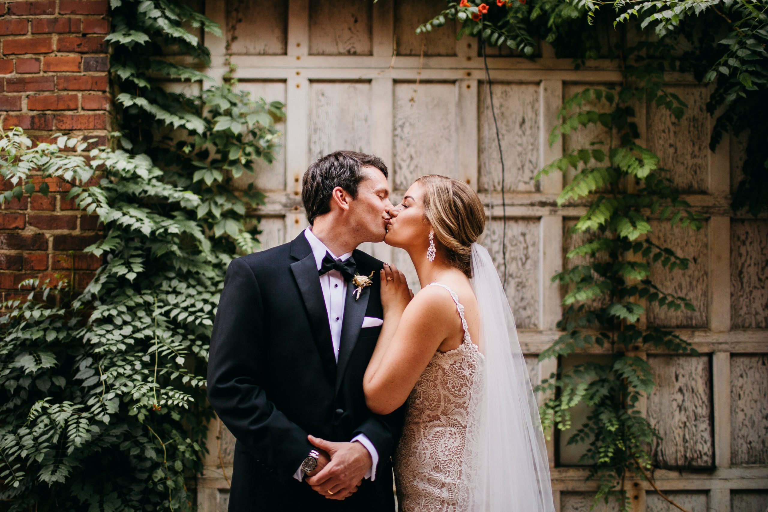 bride and groom kiss in front of ivy-covered white wooden wall