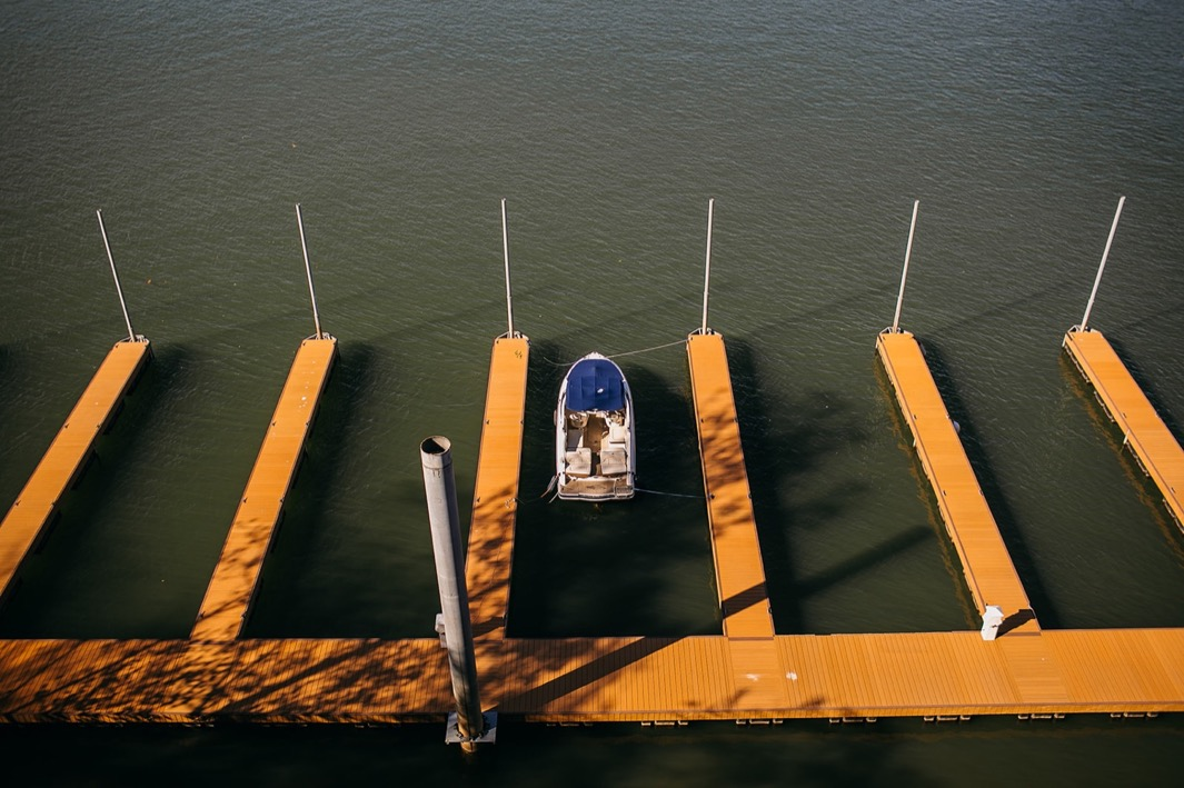 one boat sits in the middle of several empty boat slips