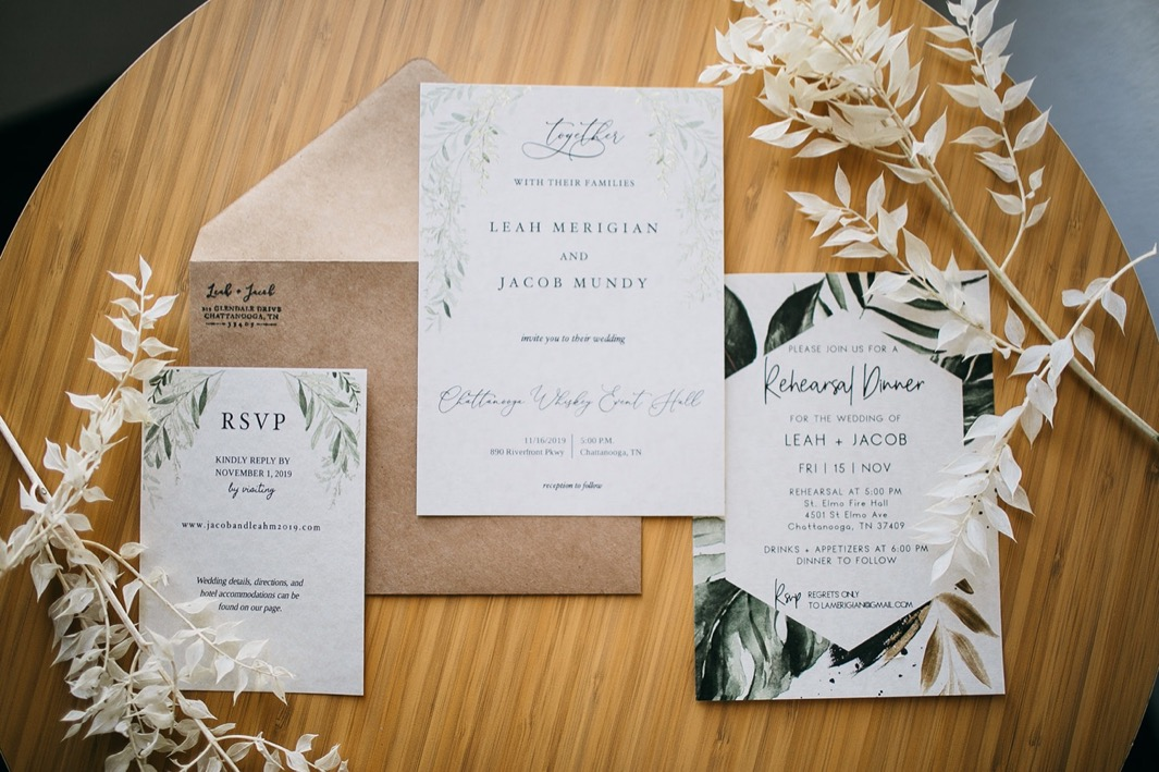 wedding invitation suite printed with watercolor greenery sits on a wooden table surrounded by white florals