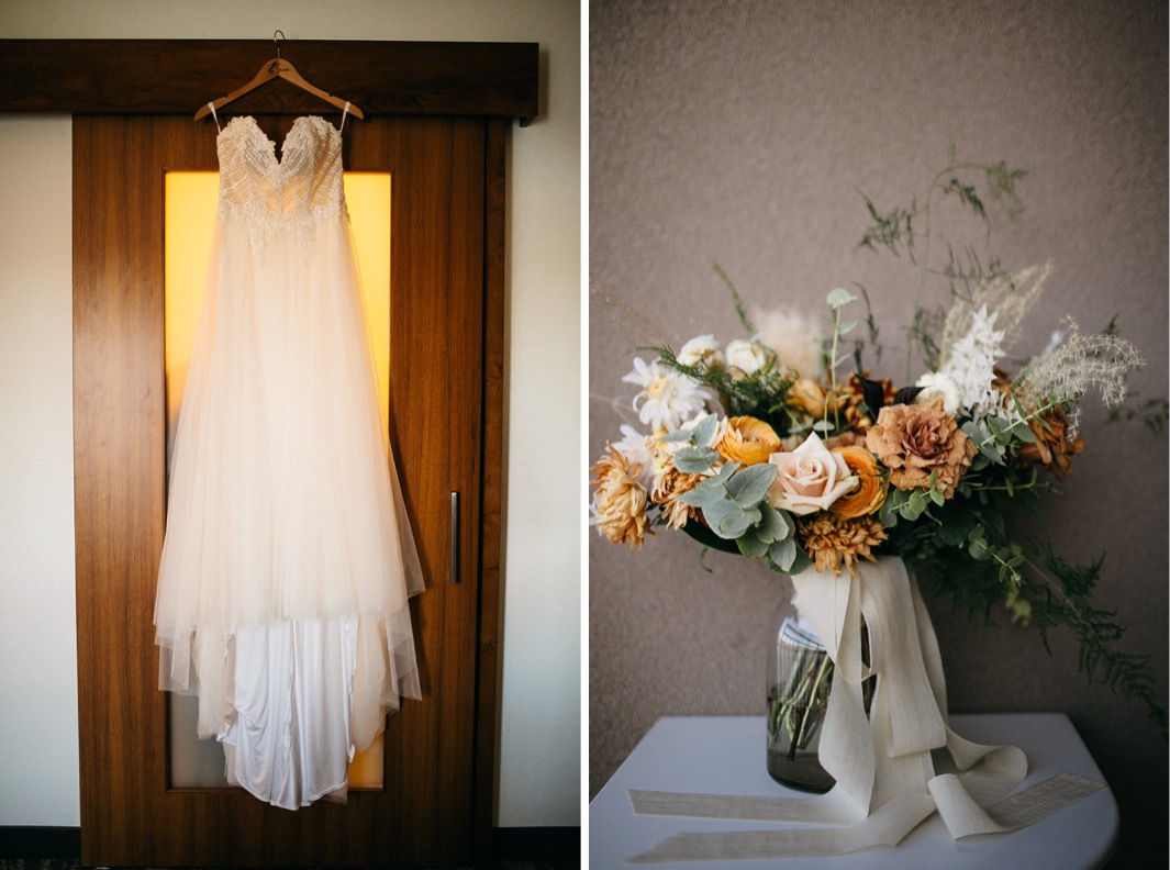 brides dress hangs over a wooden framed door while Southerly Flower Farm bouquet tied with white ribbon sits in a mason jar
