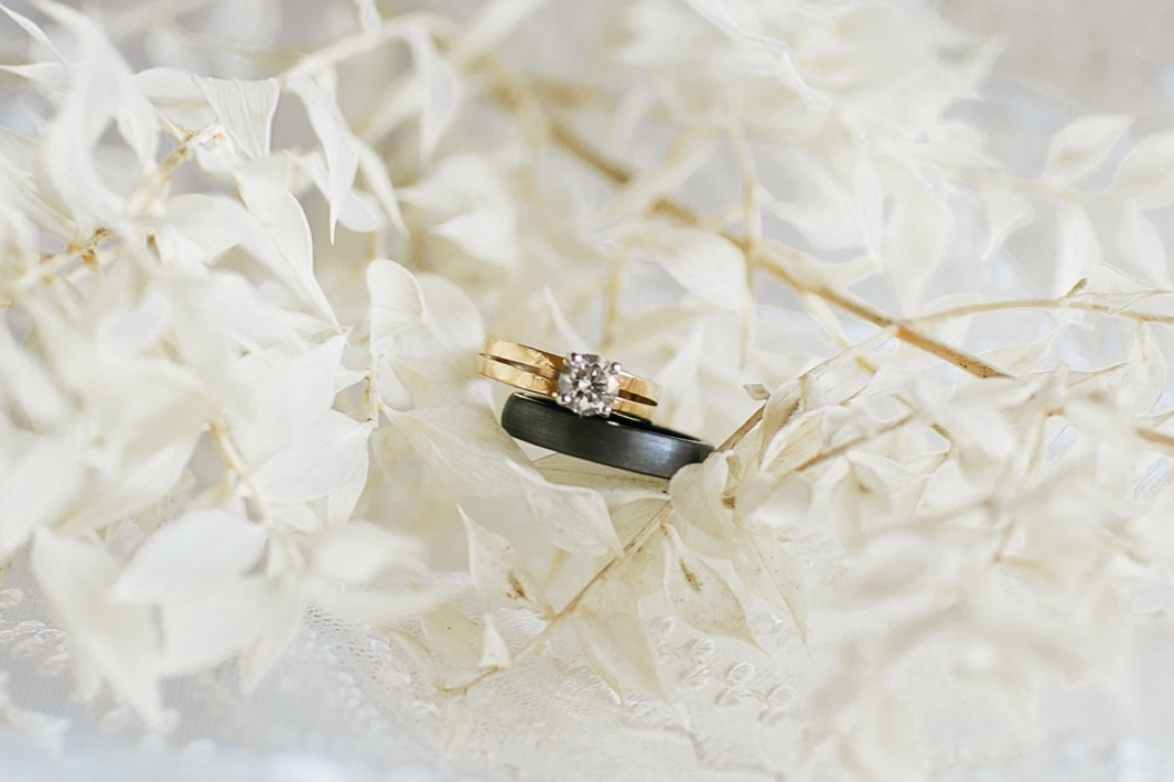 diamond wedding ring and dark wedding band sit in white floral branches
