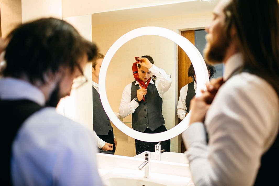 men tie their ties in front of a large bathroom mirror