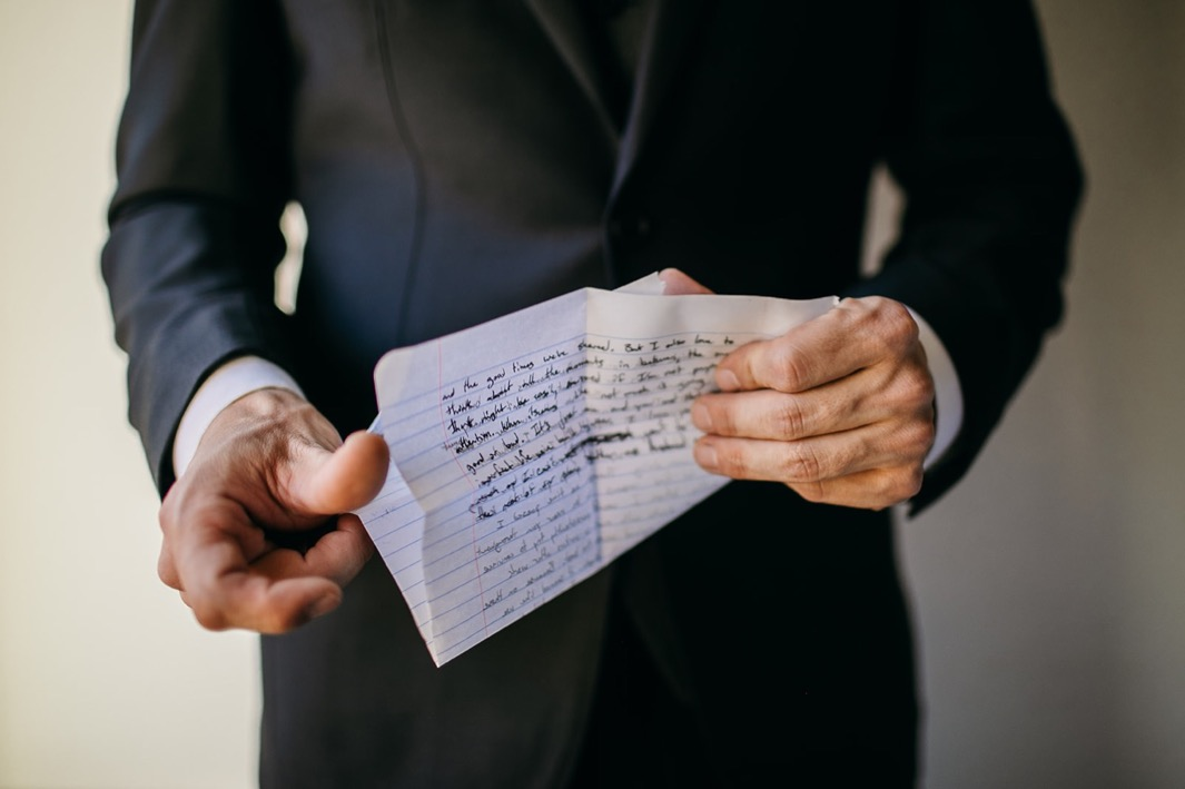 groom unfolding his handwritten vows on notebook paper