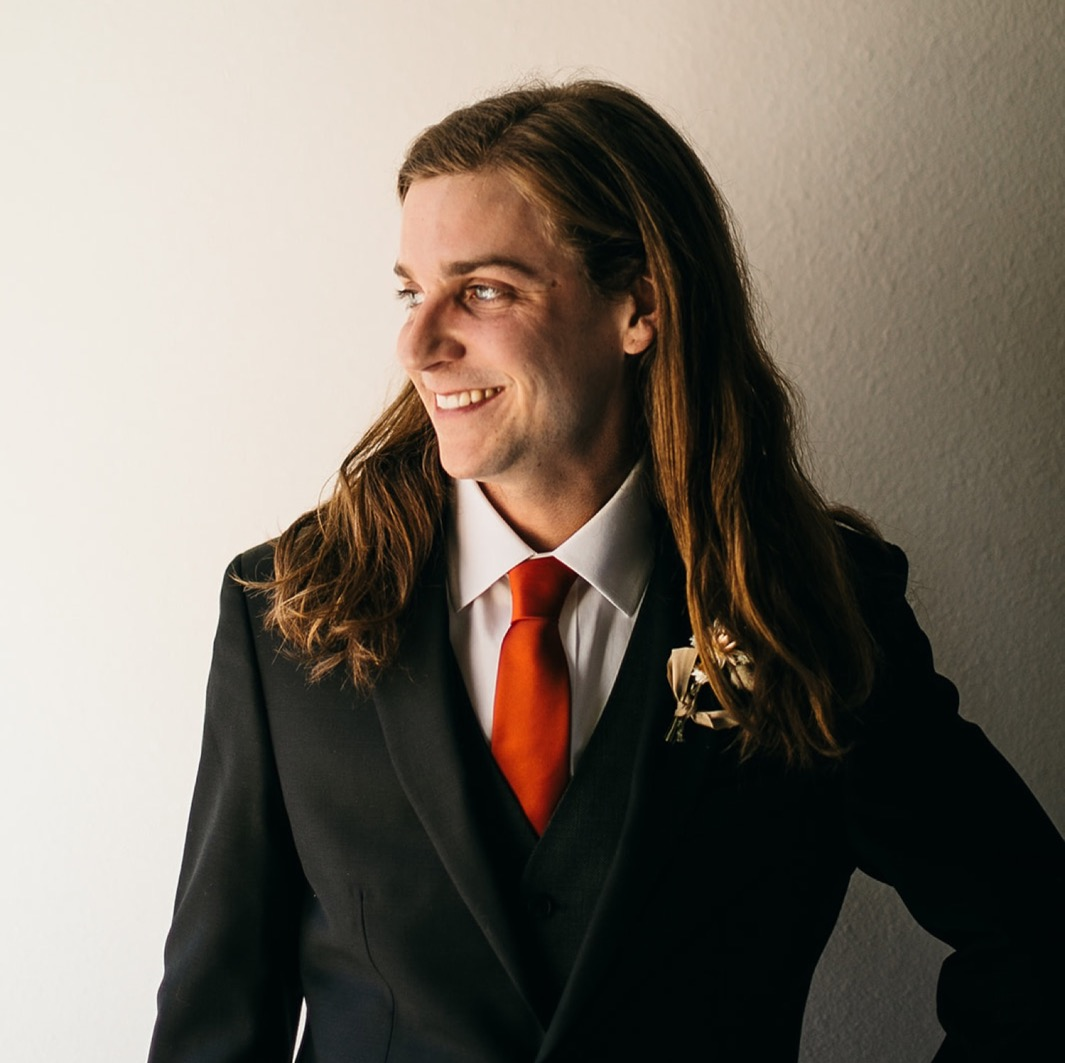 groom in dark jacket and vest over red tie and white shirt smiles
