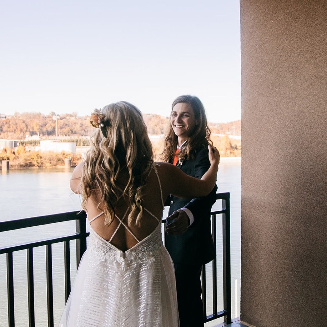 bride walks onto porch overlooking the Tennessee River to greet her groom as he turns and smiles