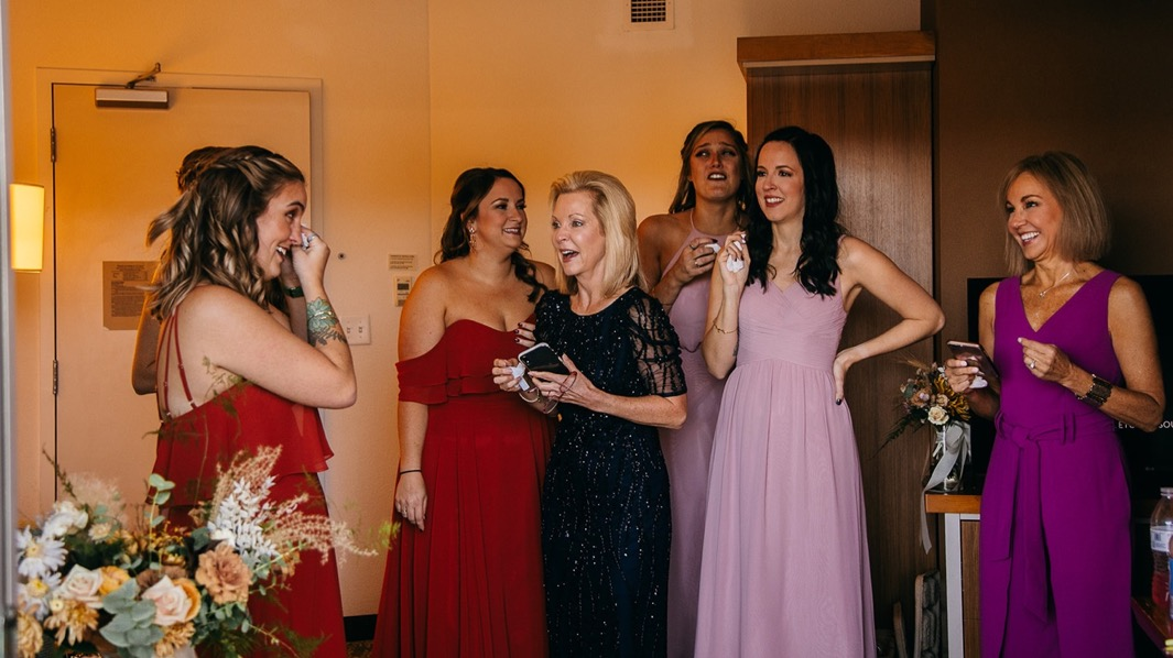 women in colorful dresses stand in a hotel room