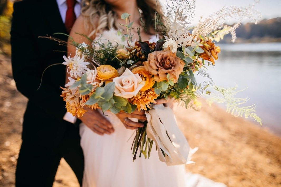 Southerly Flower Farm bridal bouquet of cream, burnt orange, and dusty pink florals among greenery