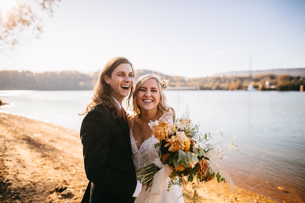 bride and groom laugh on the bank of the Tennessee River. she holds a large Southerly Flower Farm bouquet