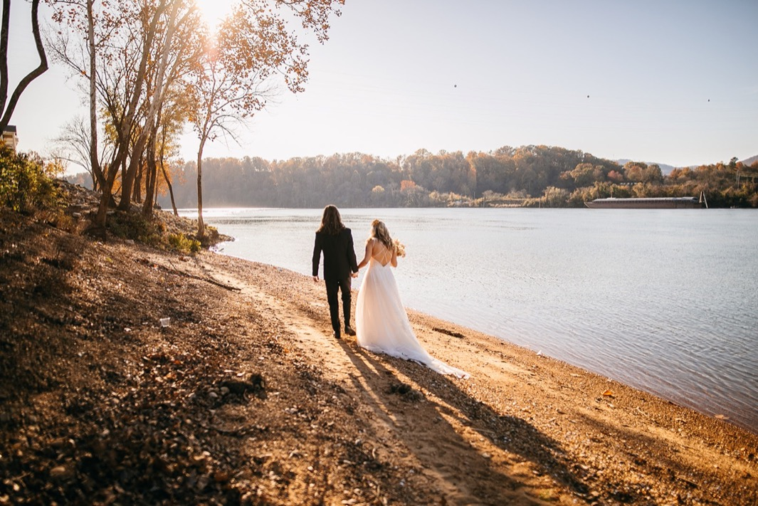 bride and groom hold hands and walk along the bank of the Tennessee River near the Chattanooga Whiskey Distillery