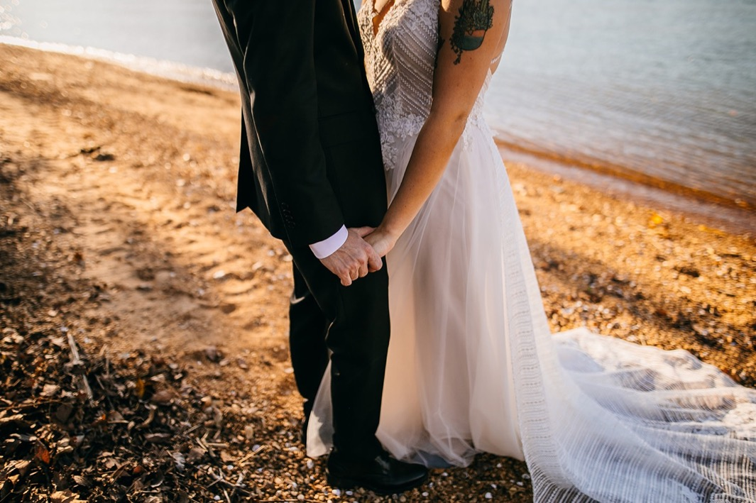 bride and groom hold hands next to the Tennessee River with her gowns train spread behind her