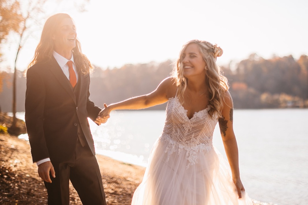 bride and groom laugh as she pulls on his hand next to the Tennessee River