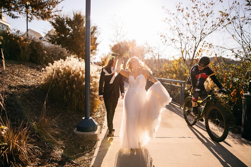 bride and groom walk along the Tennessee River Walk while a biker cycles past them