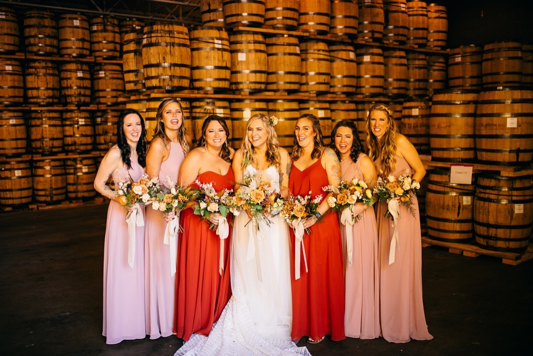 bride and bridesmaids hold Southerly Flower Farm bouquets by stacks of barrels at Chattanooga Whiskey Distillery wedding