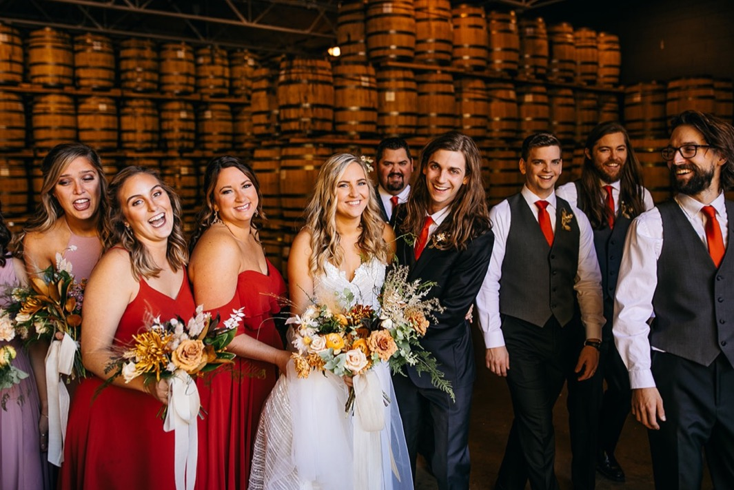 bridal party poses in a line by stacks of barrels at Chattanooga Whiskey Distillery wedding