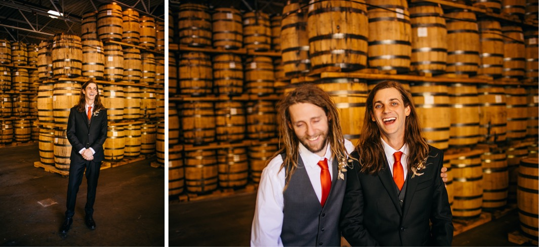 groom and groomsman stand by stacks of barrels at Chattanooga Whiskey Distillery wedding