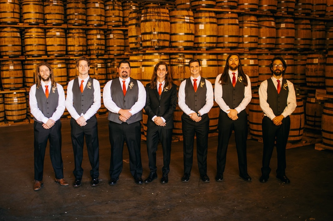 groom and groomsmen pose in a line by stacks of barrels at Chattanooga Whiskey Distillery wedding