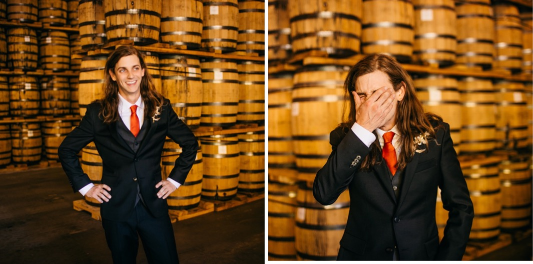 groom covers his face while laughing near stacks of barrels at Chattanooga Whiskey Distillery wedding